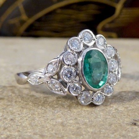 Contemporary 0.75ct Emerald and Diamond Cluster Ring with Shoulders in Platinum